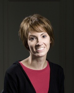 A woman with short brown hair, a black jacket, and a pink shirt smiling.